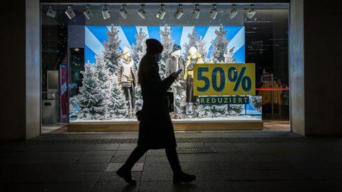 Christmas Online-Shopping: Frau geht an Schaufenster mit Weihnachtsdeko vorbei