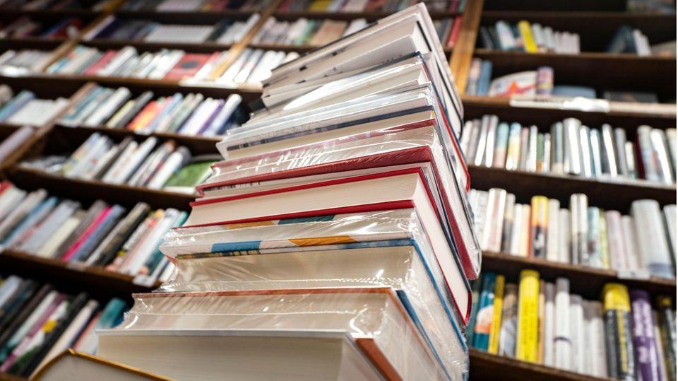 Ein Stapel neuer Bücher liegt auf einem Verkaufstisch in einer Buchhandlung