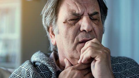 Älterer Mann mit Halsschmerzen