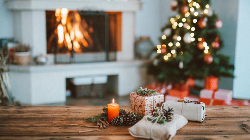 Geschenke liegen auf dem Tisch, im Hintergrund ein Weihnachtsbaum