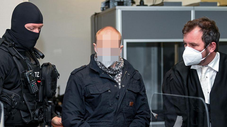 Der Angeklagte von Halle steht im Gerichtssaal zwischen einem vermummten Polizisten und einem Mann iin Robe