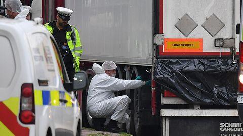 Ein Polizist in neongelber Jacke beobachtet einen Kriminaltechniker in weißem Overall, der neben einem Lkw-Auflieger kneit