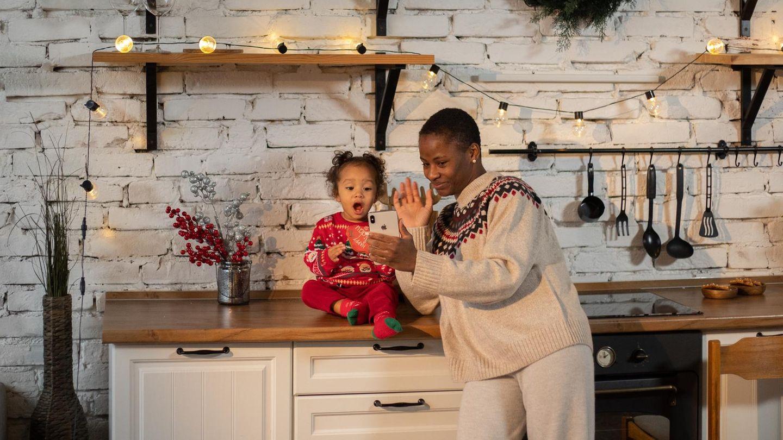 Mutter und Kleinkind sitzen in einer weihanchtlich geschmückten Küche