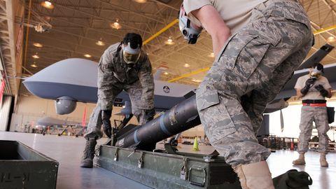 Zwei US-Soldaten munitionieren eine Drohne mit Hellfireraketen.