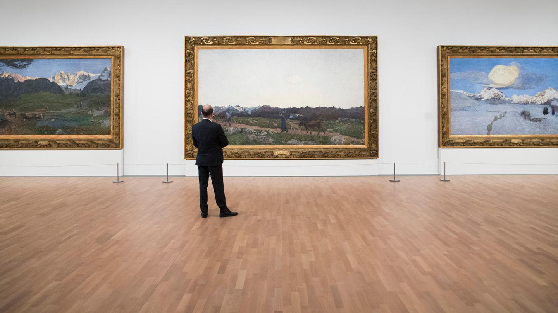 Ein älterer Mann betrachtet Bilder in einem Museum