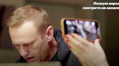 Eine Frau filmt mit einem Smartphone, wie der Kremlkritiker Alexej Nawalny mit einem mutmaßlichen Agenten telefoniert