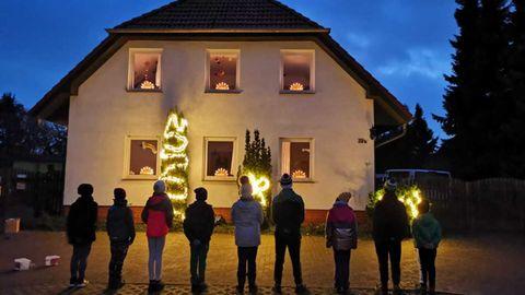 Neun Kinder stehen vor dem beleuchteten Kinderdorfhaus