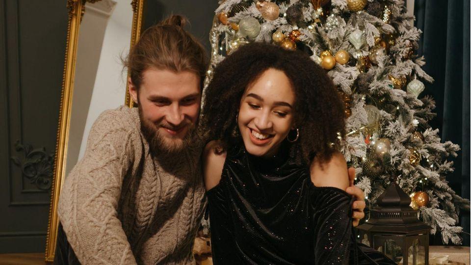 Ein junges Paar vor dem Weihnachtsbaum