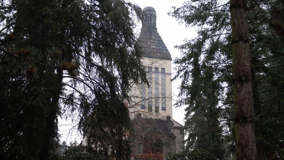 The square and sand-coloured tower of the Zittau crematorium can be seen between fir trees