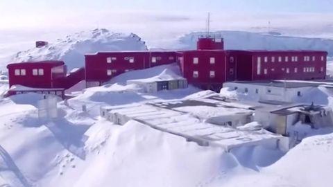 Mitten in einer schneebedeckten Landschaft ohne Bäume steht eine roter, dreistöckiger Gebäudekomplex mit Flachdach