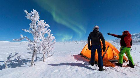 Zwei Camper schauen sich im Schnee in Kiruna das Nordlicht (Aurora Borealis) an