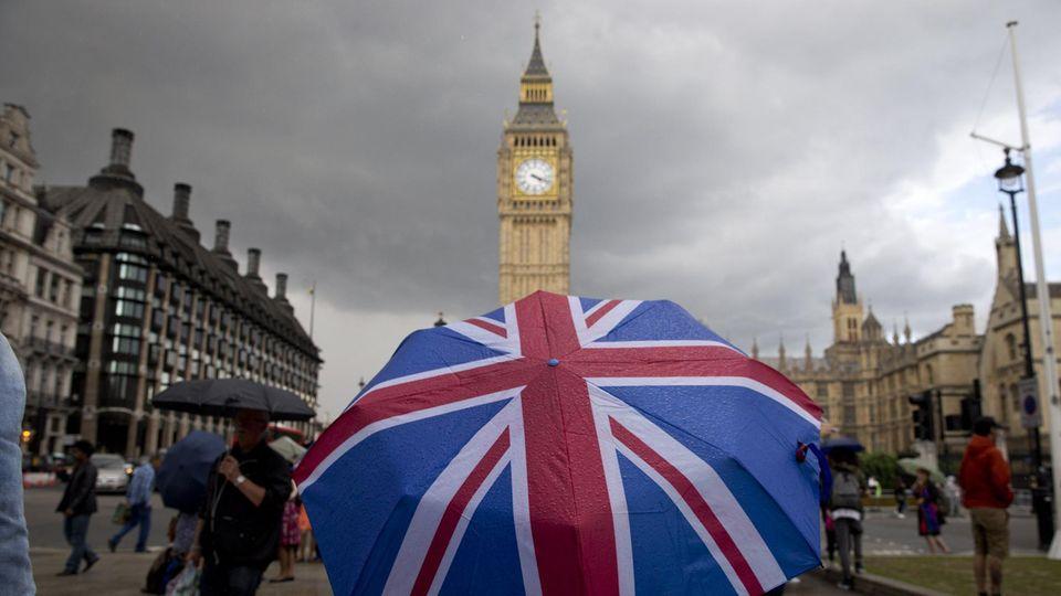 Eine Person mit einem Union-Jack-Regenschirm steht vor Big Ben in London