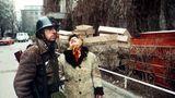 """Das Jahr 1989 war das Jahr, in dem der Eiserne Vorhang fiel und es in vielen kommunistischen und sozialistischen Staaten des Ostblocks–etwa in Ungarn, Polen und der DDR–zu friedlichen Regimewechseln und später zu freien Wahlen kam. In Rumänien verlief die Revolution blutig, wie dieses Foto zeigt.Ein Soldat steht neben einer Frau, die soeben vom Tod ihres Sohnes erfahren hatte, aufgenommen am 25.12.1989. Nach dem Sturz des Diktators Nicolae Ceausescu am 22. Dezember 1989 herrschten in Rumänien bürgerkriegsähnliche Zustände. Mitglieder der Geheimpolizei Securitate, Schergen des selbsternannten """"Conducator"""" (Führer) Ceausescu, lieferten sich mit der auf der Seite des Volkes kämpfenden Armee erbitterte Kämpfe. Ceausescu und seine Frau wurden auf der Flucht verhaftet und am 25. Dezember 1989 von einem militärischen Sondergericht zum Tode verurteilt und erschossen. Nach der Hinrichtung herrschte große Befriedung in Rumänien, aber kein Jubel."""