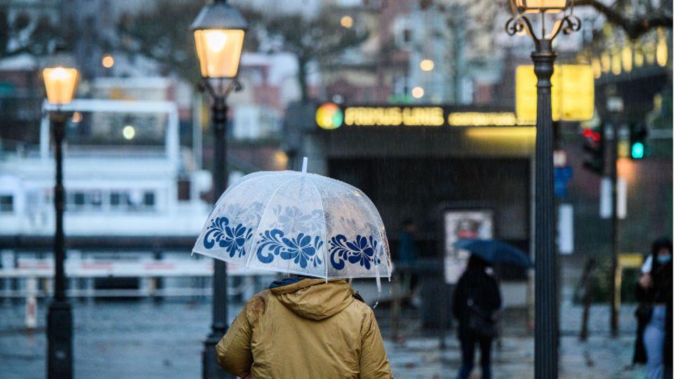 Eine Frau geht mit ihrem Schirm über den Römerberg in Frankfurt