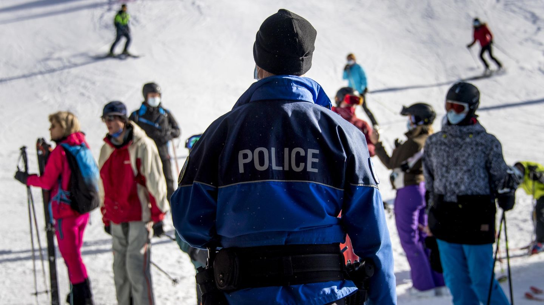 Ein Polizist kontrolliert Ski-Fahrer auf einer Piste im Walliser Skigebiet auf das Tragen von Mund-Nasen-Bedeckungen.