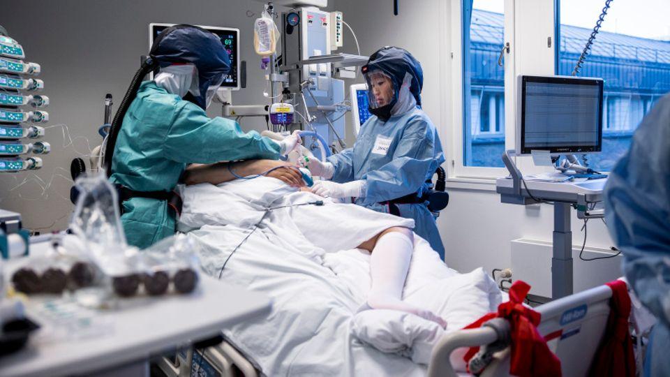 Norwegen, Oslo: Die Krankenschwestern Inika and June Flaa behandeln in Schutzkleidung einen Corona-Patienten