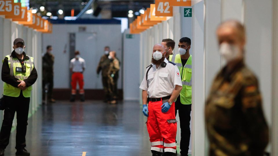 Berlin: Mitarbeiter des Deutschen Roten Kreuzes (DRK), der Bundeswehr und Helfer warten im Impfstoffzentrum Arena Treptow auf den Beginn der Impfungen gegen das Coronavirus