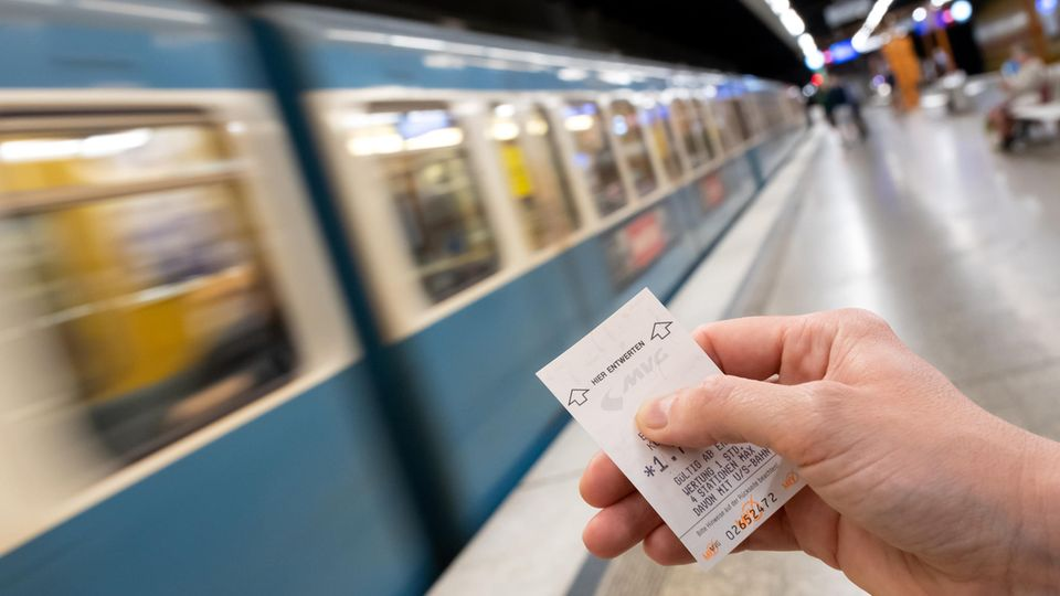 Eine Frau hält an einer U-Bahn-Station in München ein MVG-Ticket in der Hand