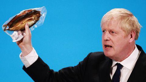 Boris Johnson hält einen eingeschweißten Räucherfisch hoch