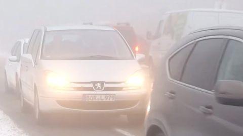 Im Nebel stauen sich auf einer Straße Autos mit Licht an. Neben der Straße liegt Schnee