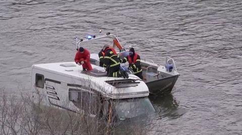 Auf dem Dach eines bis zur Windschutzscheibe im Rhein versunkenen Wohnmobils knien zwei Feuerwehrleute. Daneben ein Boot