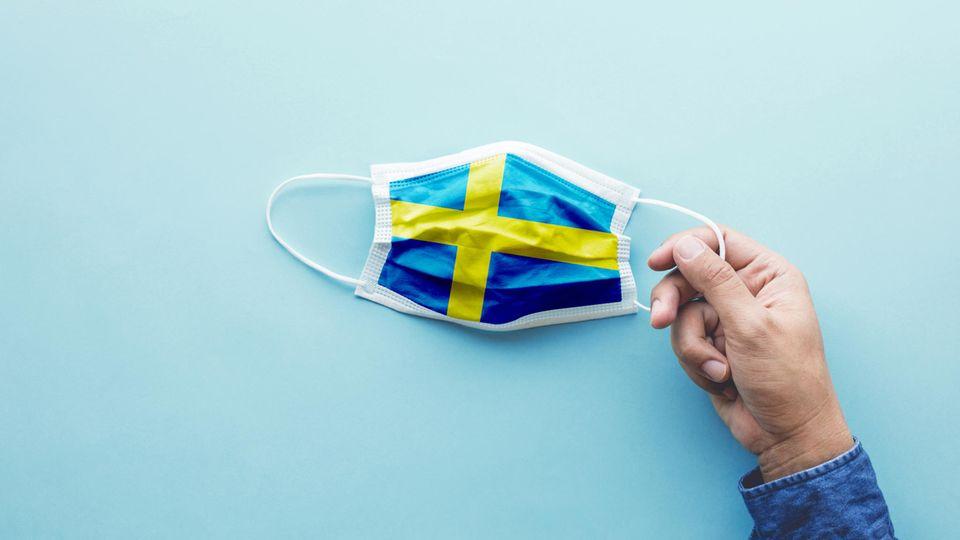 Eine Hand hält einen Mund-Nase-Schutz mit der schwedischen Flagge als Motiv