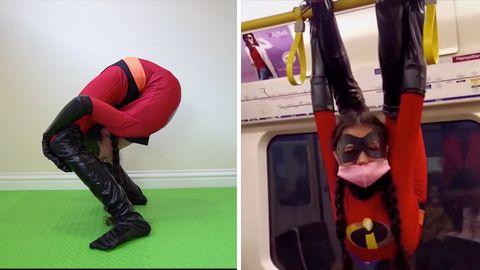 Ein Mädchen in einem rot-schwarzen Superhelden-Anzug beugt sich so weit nach hinten, dass ihr Kopf zwischen den Knien ist