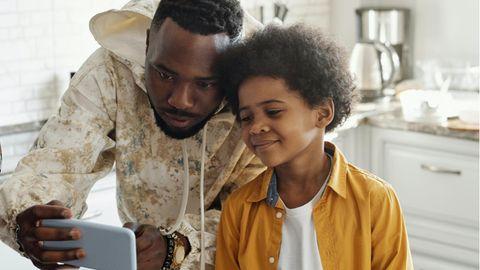 Ein Vater zeigt seinem Sohn ein Video auf dem Handy