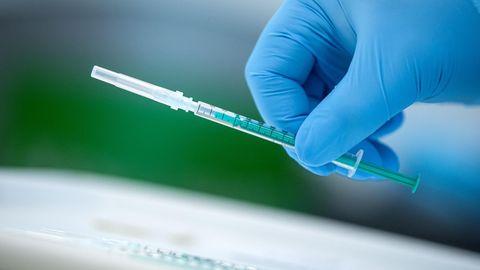 Bremen: Ein Mitarbeiter vom Impfzentrum hält eine Spritze mit dem Covid-19-Impfstoff in der Hand