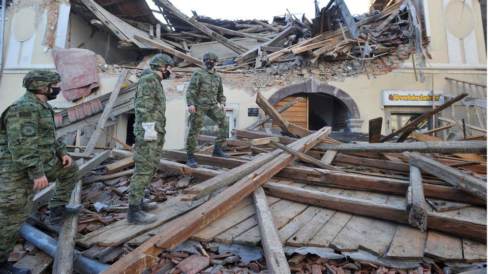Soldaten inspizieren die Trümmer eines vom Erdbeben beschädigten Gebäudes in der Stadt Petrinja