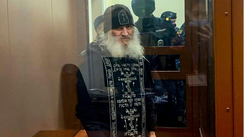 Russland, Moskau: Vater Sergij, Mönch aus Russland, steht vor einer Gerichtssitzung in einem Glaskäfig.
