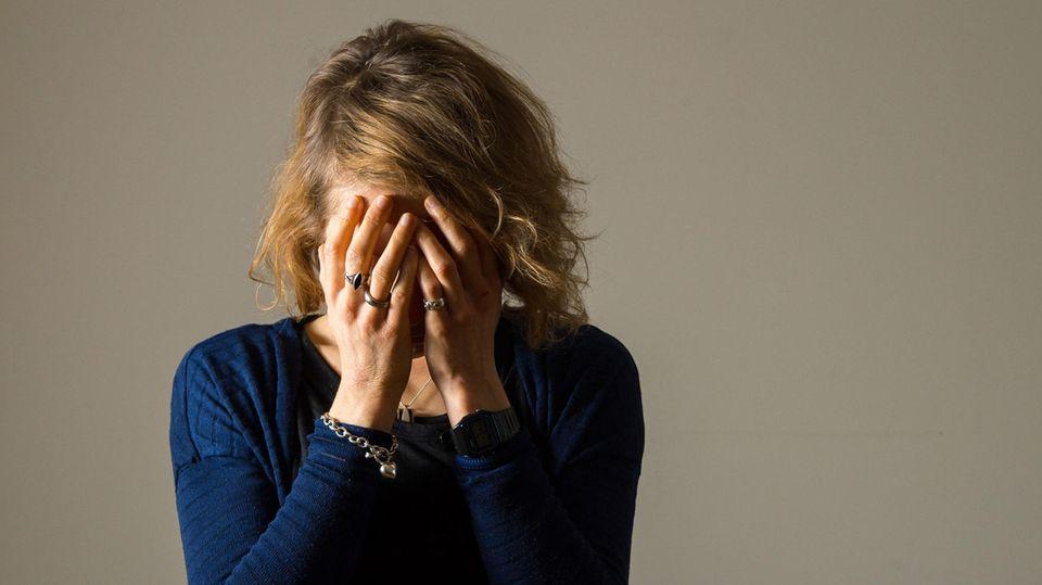 Eine weinende Frau verbirgt ihr Gesicht in den Händen