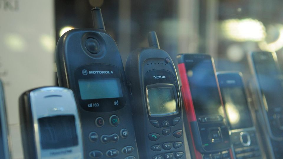 Alte Handys stehen in einem Schaufenster eines Geschäfts