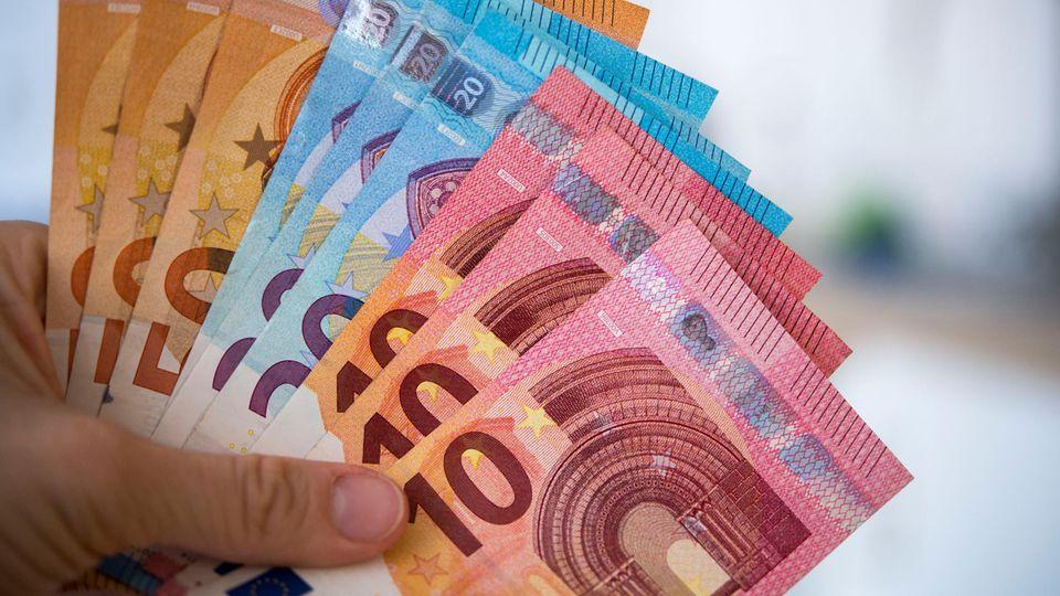 Die linke Hand einer Frau hält aufgefächert 10-, 20- und 50-Euro-Scheine