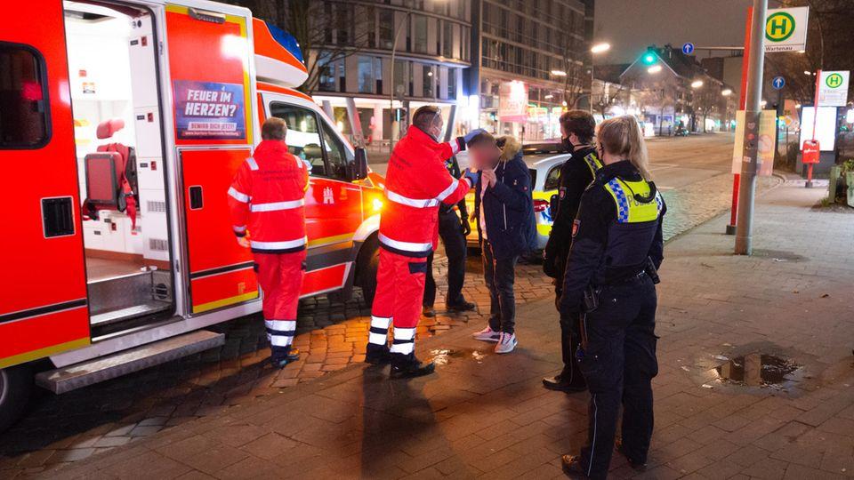Ein Rettungsassistent in Hamburg wäscht einer verletzten Person die Augen aus