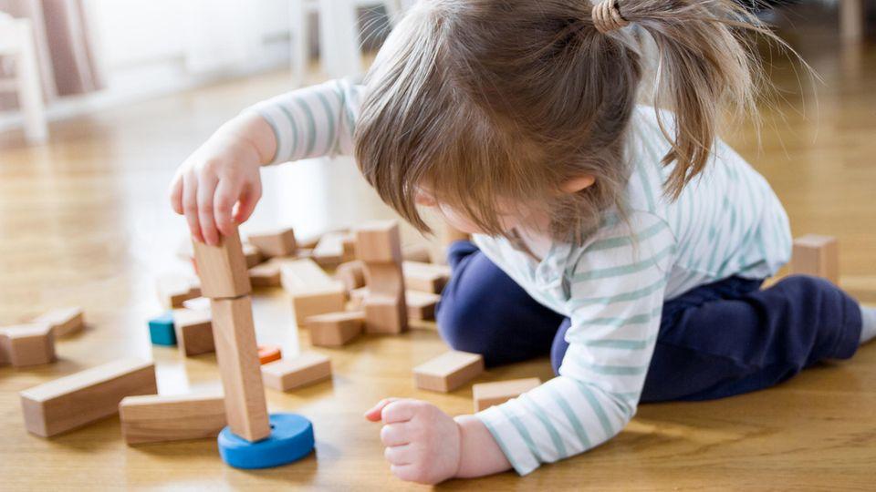 Ein Mädchen spielt mit Holzspielzeug