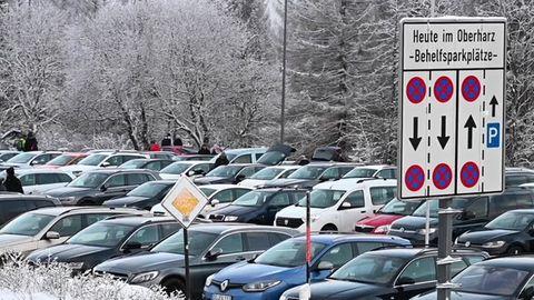 Auf einem Parkplatz zwischen verschneiten Tannen und Bäumen stehen Autos dicht an dicht