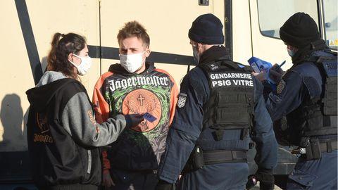 Zwei Polizisten in dunkelblauen Uniformen sprechen vor einer Halle mit einer jungen Frau und einem jungen Mann in Party-Outfits
