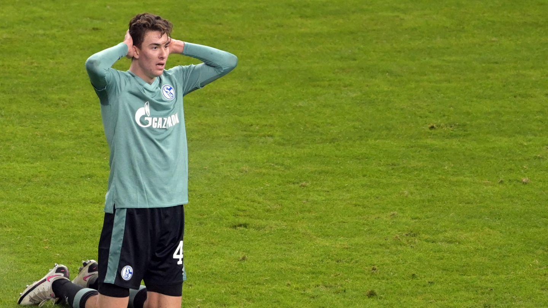 Ein Fußballer im türkisen Trikot und schwarzer Hose kniet auf dem Rasen und schlägt die Hände über dem Kopf zusammen