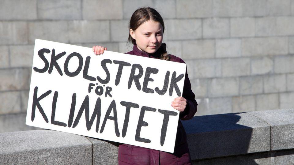 """Die schwedische Klimaaktivistin Greta Thunberg hält ein Schild mit Aufschrift """"Skolstrejk för klimatet"""" hoch"""