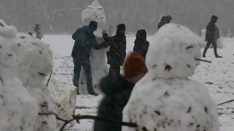 Auf einer verschneiten Wiese steht eine Schneemann-Familie. Im Hintergrund bauen Kinder einen weiteren Schneemann