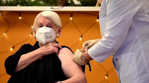 Eine schwarz gekleidete ältere Frau im Rollstuhl bekommt von einem Mann im weißen Kittel eine Spritze in den linken Oberarm
