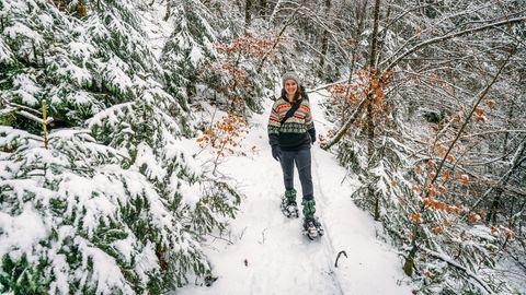 Frau im Wald mit Schneeschuhen