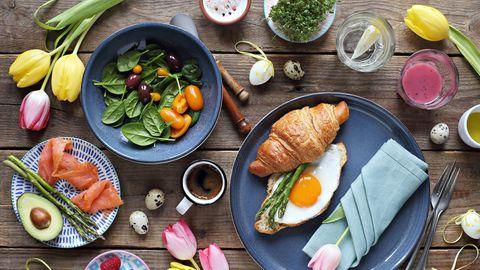 Frühstück mit Croissant, Spiegelei, Lachs, Avocado, Salat