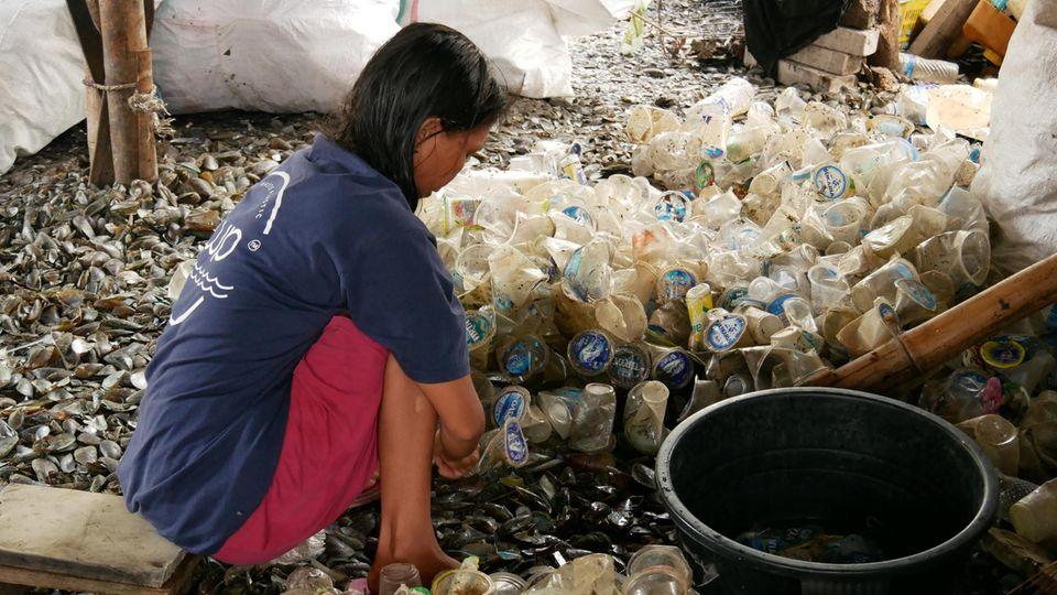 Eine Muschelsammlerin sortiert Plastikbecher