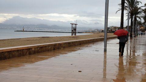Ein Mann spaziert mit einem Regenschirm am Strand von Palma entlang.