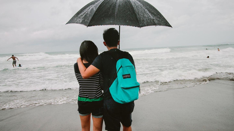 Ein Paar steht bei Sturm an einem Strand