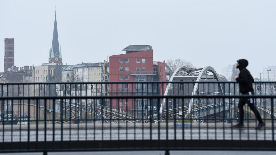 Ein Mann joggt über die Brücke am Bahnhof Ostkreuz in Berlin