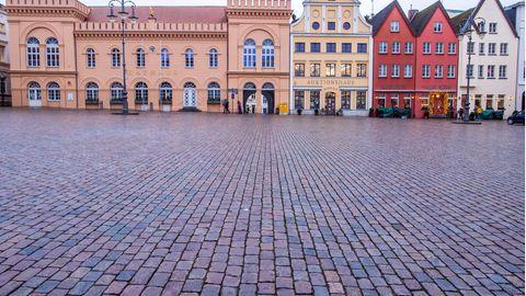 Das historische Rathaus in Schwerin und Handelshäuser stehen am leeren Marktplatz