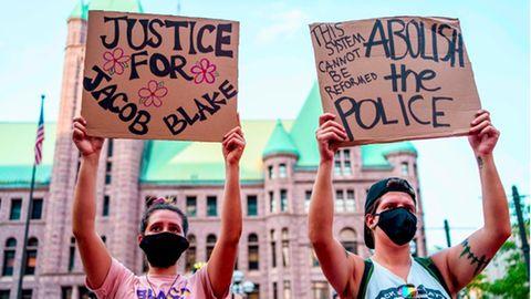 Zwei Amerikaner protestieren gegen Polizeigewalt in den USA und fordern Gerechtigkeit für Jacob Blake.